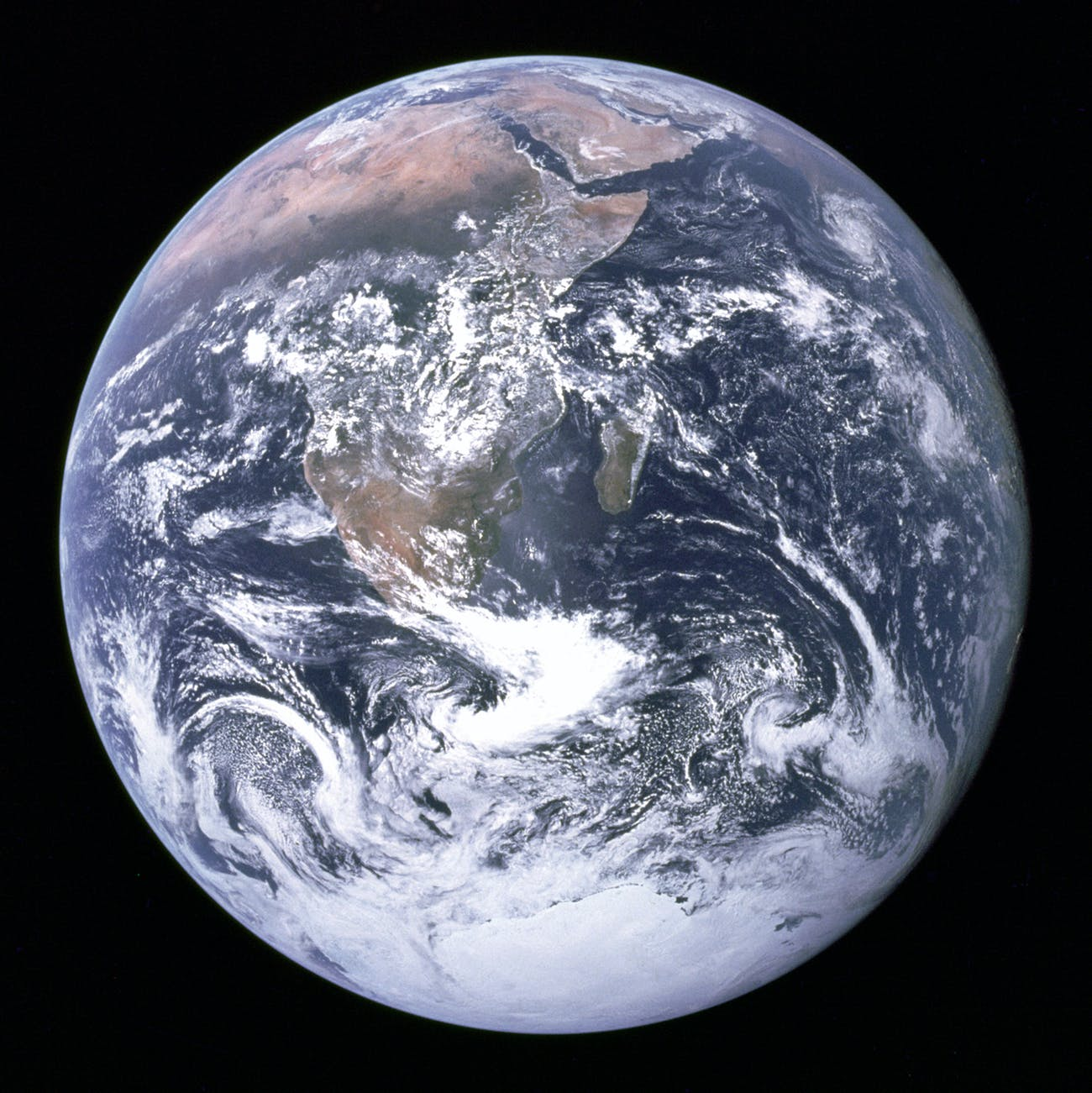 """The Blue Marble"" is a famous photograph of the Earth taken on December 7, 1972, by the crew of the Apollo 17 spacecraft en route to the Moon at a distance of about 18,000 miles. It shows Africa, Antarctica, and the Arabian Peninsula."