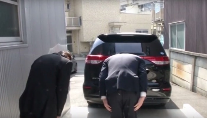 Members of the staff bowing as they say goodbye to one of their guests