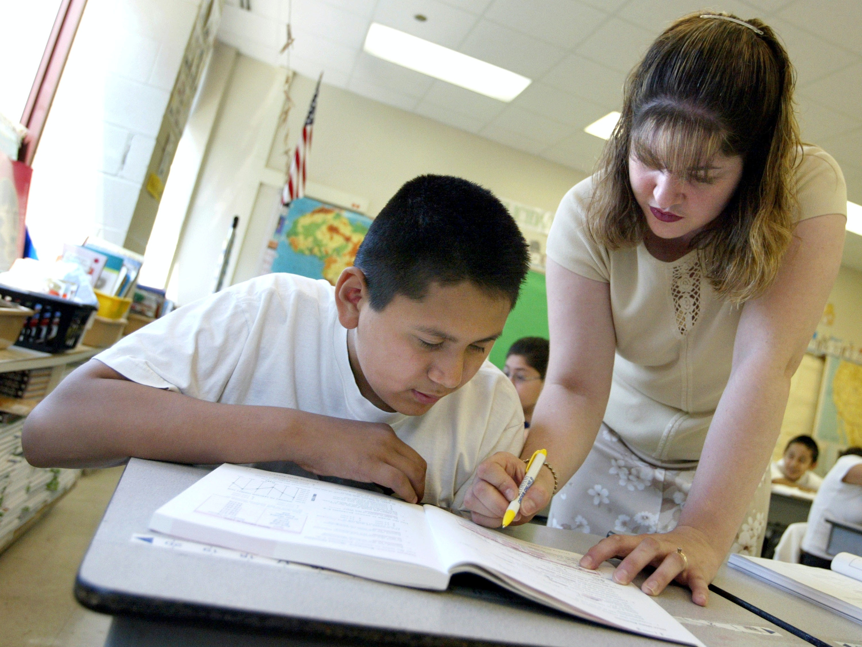 CHICAGO, IL - JULY 2:  Teacher Blanca Feliciano assists a student in her sixth-grade class during summer school July 2, 2003 in Chicago, Illinois. A record number of students are expected at summer school due to a strong showing for a new voluntary program for mid-tier students and strict application of non-ITBS (Iowa Tests of Basic Skills) test promotion standards.  (Photo by Tim Boyle/Getty Images)