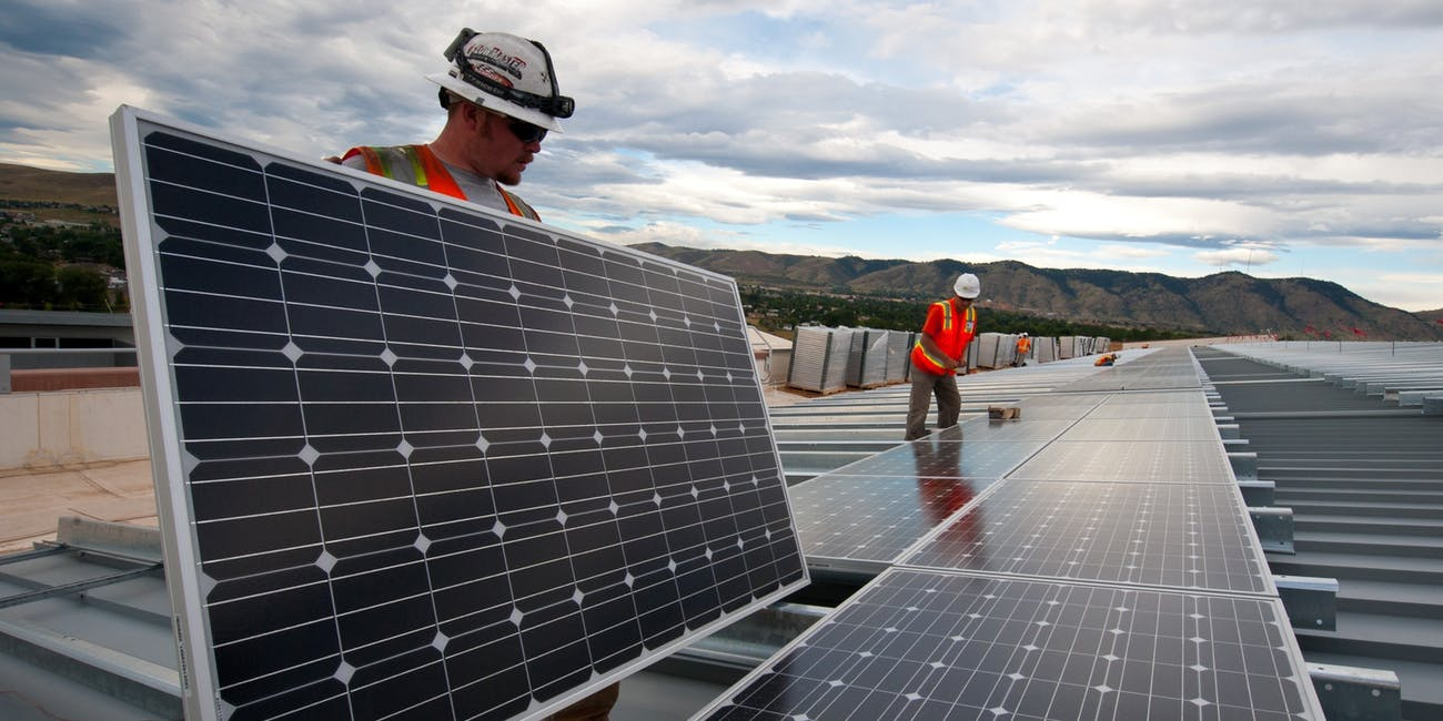 An image shows men installing solar panels.
