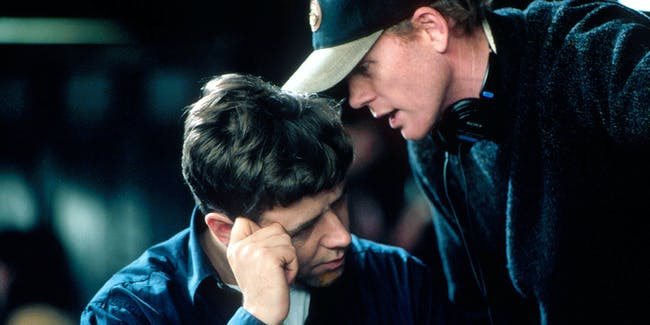 401864 09: (EDITORIAL USE ONLY, COPYRIGHT MCA/UNIVERSAL PICTURES) Director Ron Howard speaks with actor Russell Crowe on the set of the film 'A Beautiful Mind.' (Photo by MCA/Universal Pictures/Getty Images)