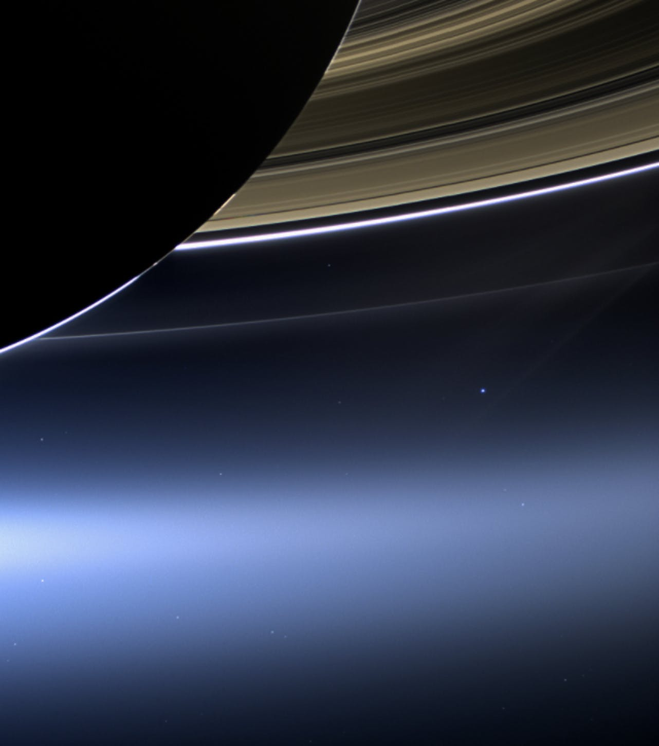 Saturn, from Cassini's perspective, along with a tiny bright dot below the rings that is Earth.