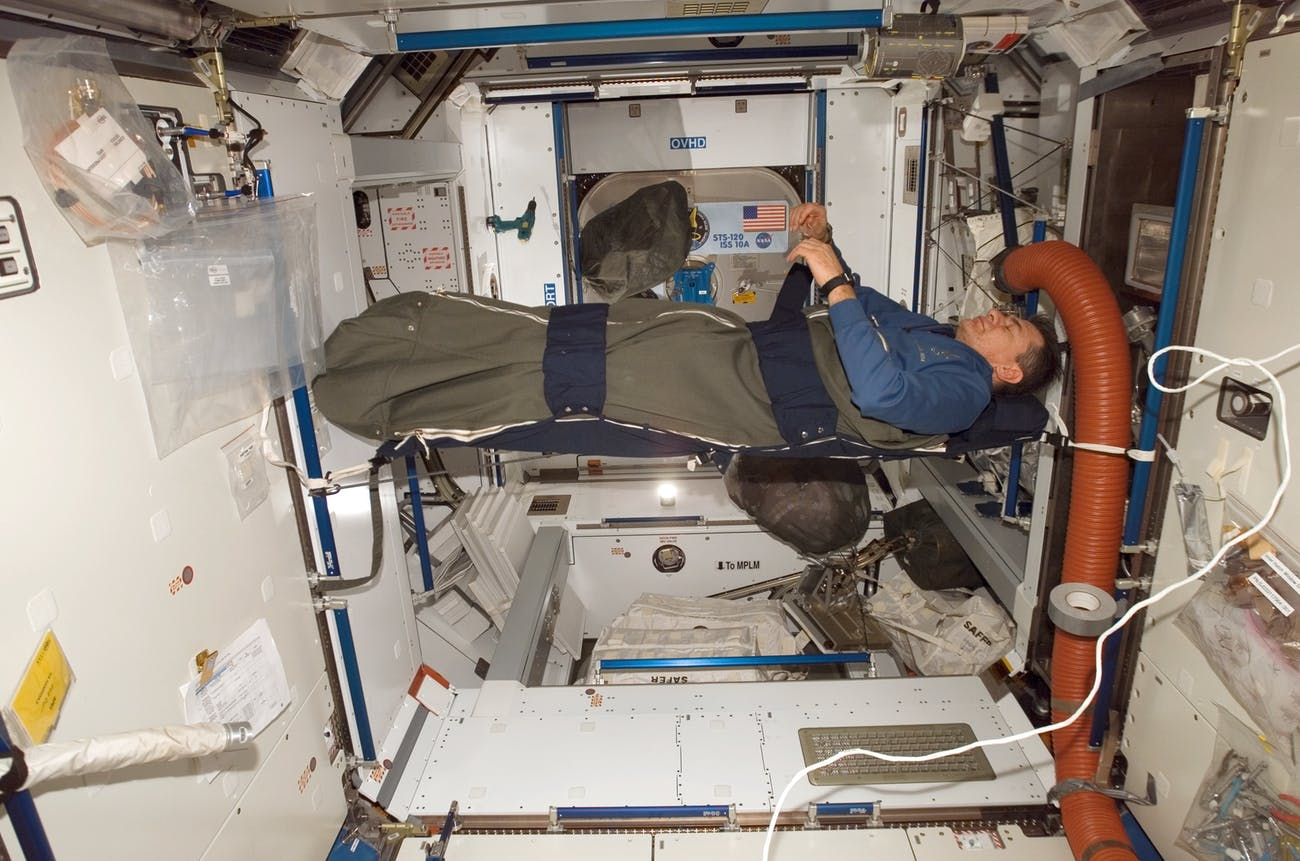 An astronaut sleeps in the International Space Station.