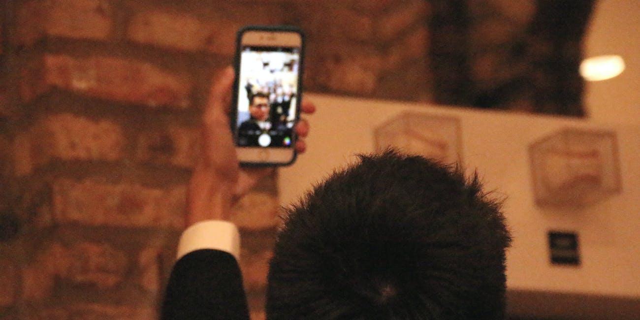 Man taking selfie on Apple phone.