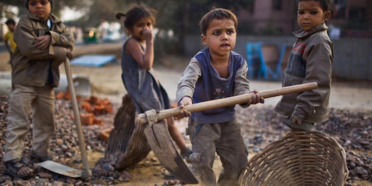 Indian children work near their parents at a construction project in front of the Jawaharlal Nehru Stadium on January 30, 2010, in New Delhi, India.