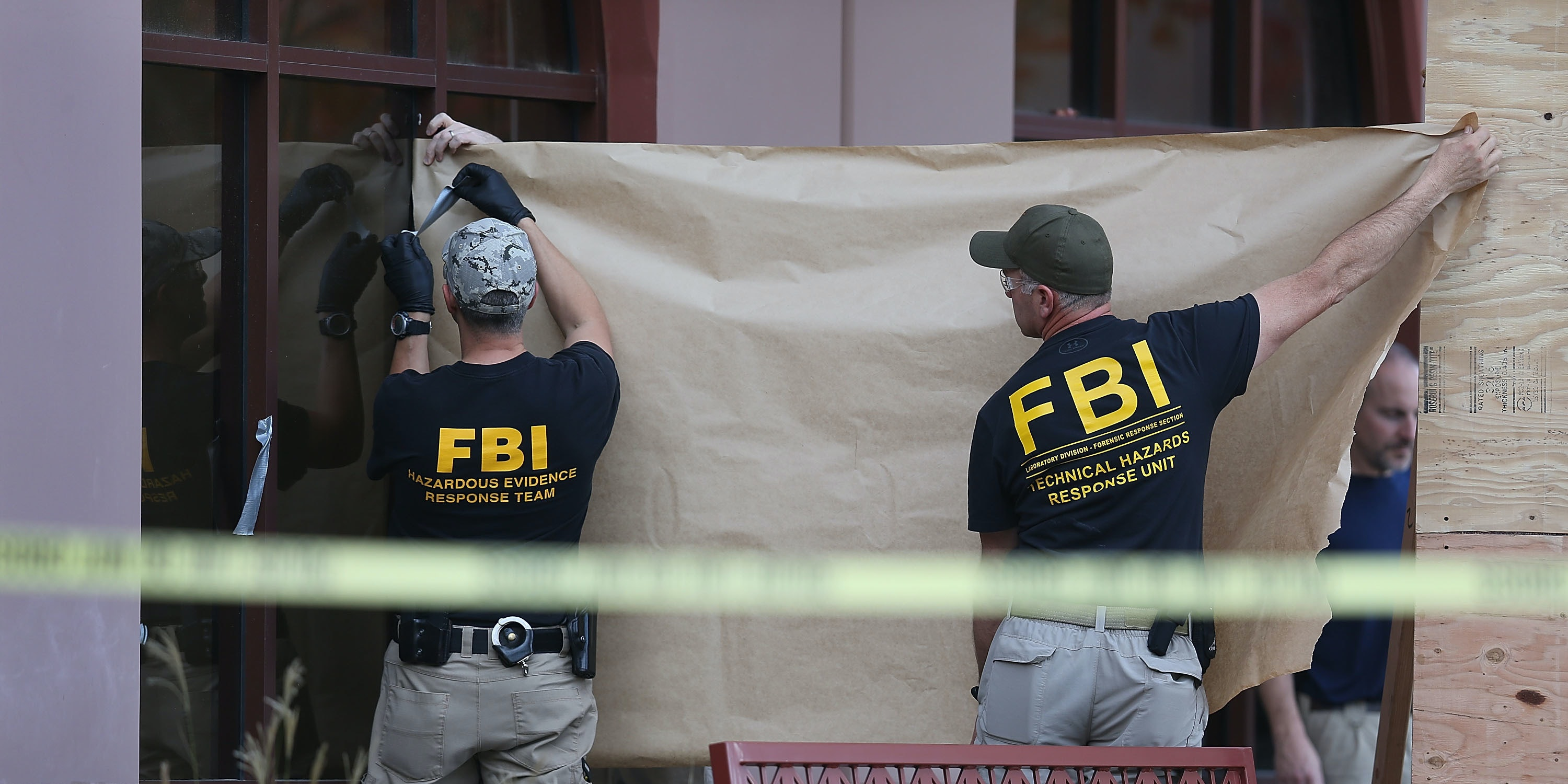 FBI agents put up a screen to block the view of onlookers as they investigate the building at the Inland Regional Center were 14 people were killed on December 7, 2015 in San Bernardino, California.