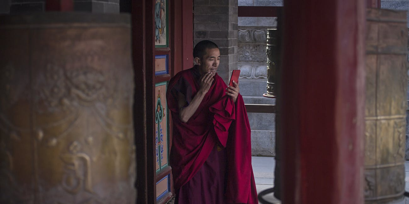 UNSPECIFIED, CHINA - APRIL 23: A Tibetan buddhist monk use iphone in the courtyard of the Kumbum Monastery on April 23, 2017 in Xining, Qinghai Province. Kumbum was founded in 1583 in a narrow valley close to the village of Lusar in the Tibetan cultural region of Amdo. (Photo by Wang He/Getty Images)