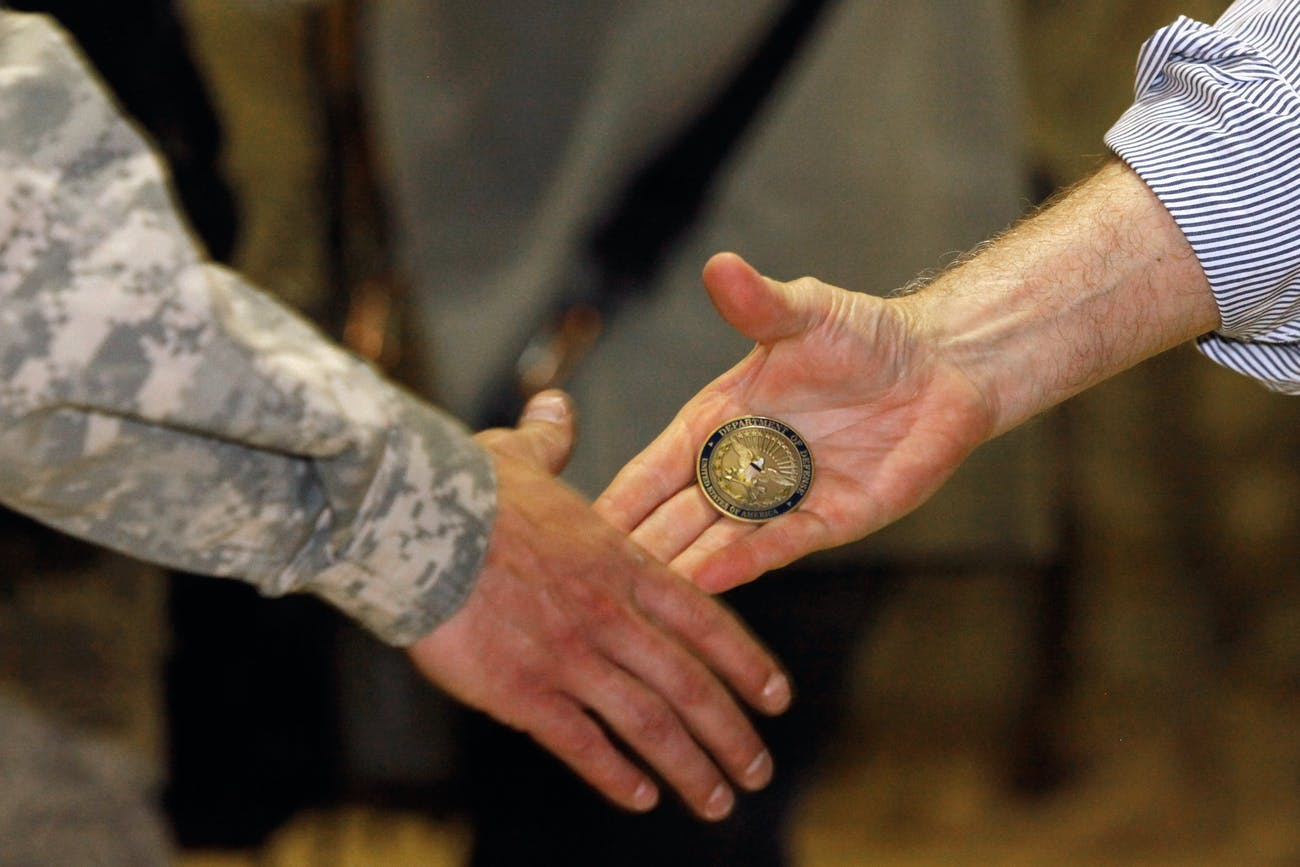 U.S. Defense Secretary Robert Gates presents a 'challenge coin' while shaking hands and posing for photographs with soldiers from the 4th Advise and Assist Brigade, 1st Calvalry Division out of Fort Hood, Texas while visiting Camp Marez in Mosul, Iraq.