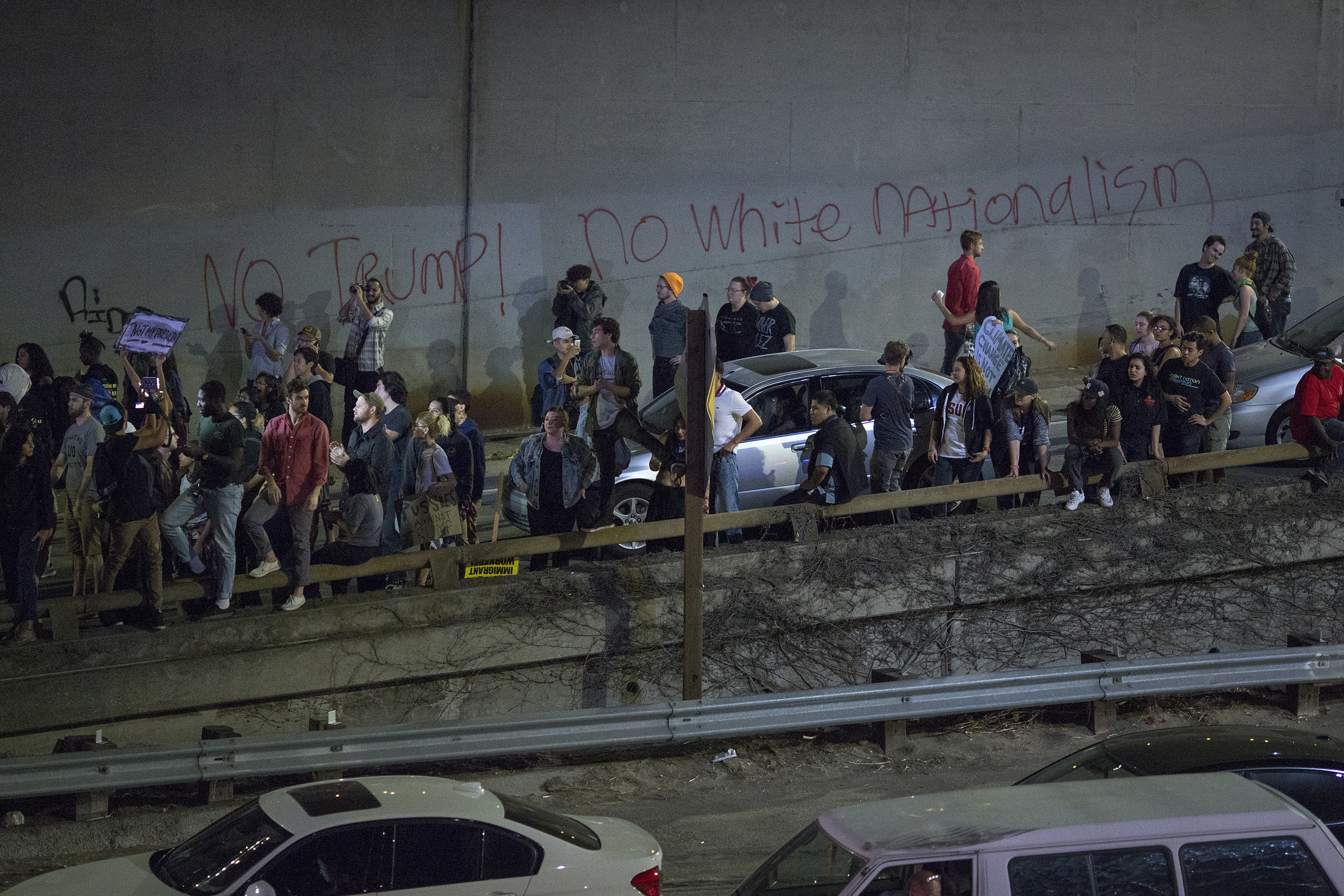 Protesters on an onramp watch as police advance toward them in Los Angeles, California.