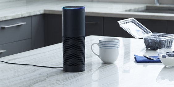 Amazon Echo sits on a kitchen table.