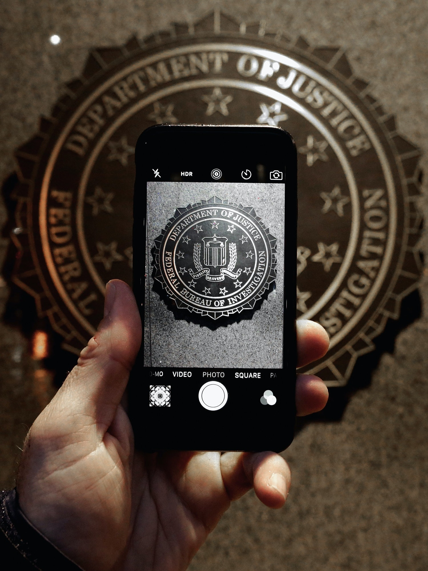 WASHINGTON, DC - FEBRUARY 23:  The official seal of the Federal Bureau of Investigation is seen on an iPhone's camera screen outside the J. Edgar Hoover headquarters February 23, 2016 in Washington, DC. Last week a federal judge ordered Apple to write software that would allow law enforcement agencies investigating the December 2, 2015 terrorist attack in San Bernardino, California, to hack into one of the attacker's iPhone. Apple is fighting the order, saying it would create a way for hackers, foreign governments, and other nefarious groups to invade its customers' privacy.  (Photo by Chip Somodevilla/Getty Images)