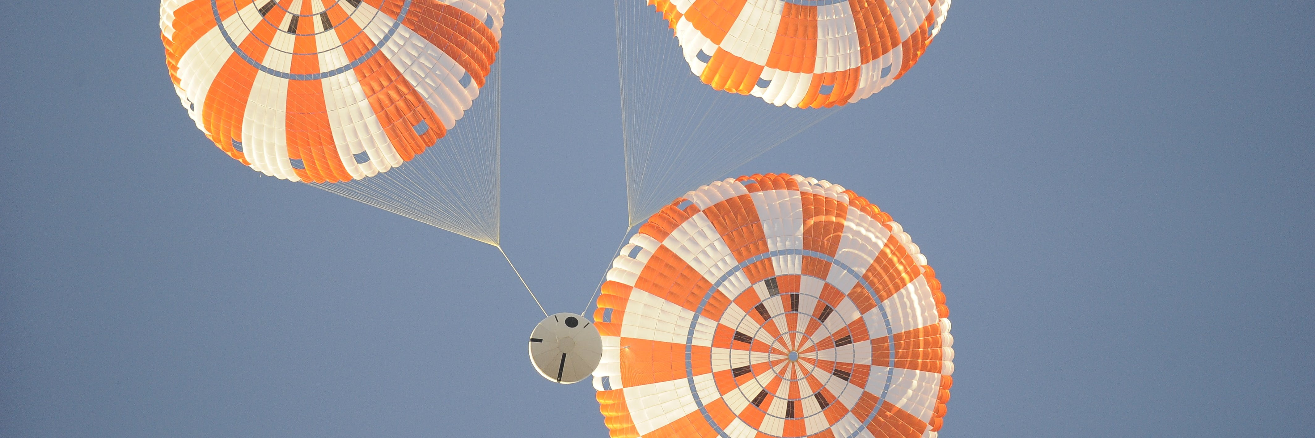 NASA's Orion spacecraft, or a model of it at least, falls from the sky on a triple parachute system.