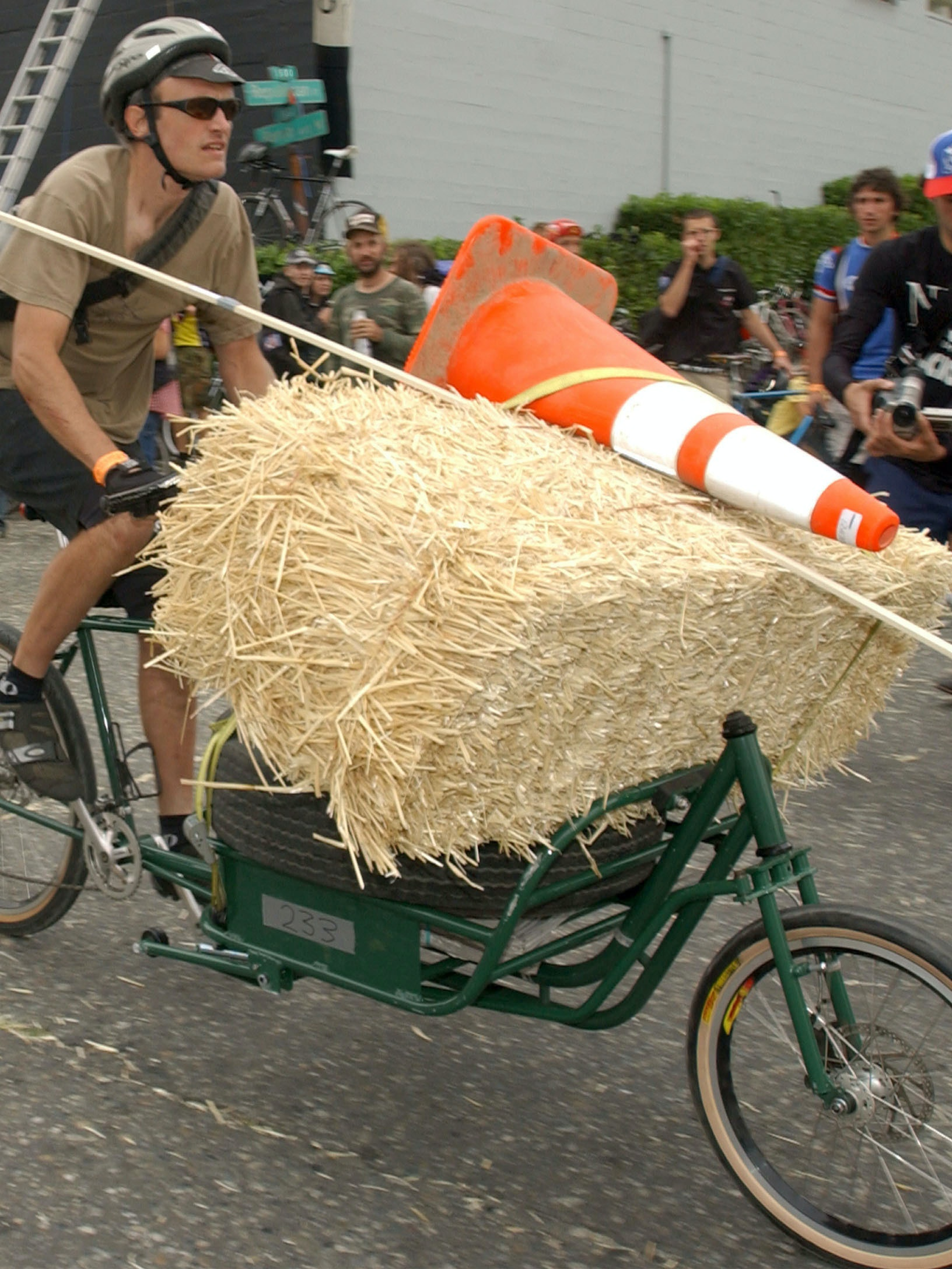 SEATTLE, WA - SEPTEMBER 14:  Robert Burchett, from Portland, Oregon,  struggles while carrying a bale of hay and a car tire on his bicycle at the 11th Annual Cycle Messenger Championships September 14, 2003 in Seattle, Washington. Burchett took part in the cargo race in which messengers had to pick up and drop off a variety of packages while battling hills, curbs, and hazards such as railroad tracks. There were over 600 participants from over six countries at the three day event.  (Photo by Ron Wurzer/Getty Images)
