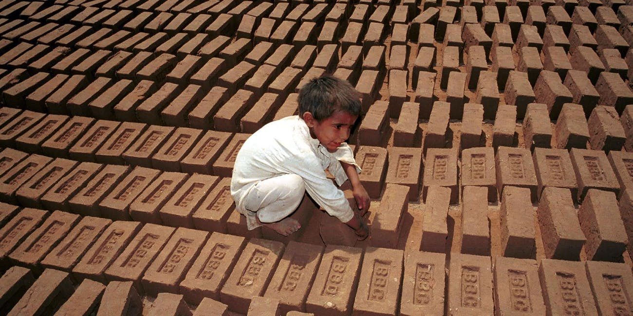 A young Pakistani boy lays bricks.