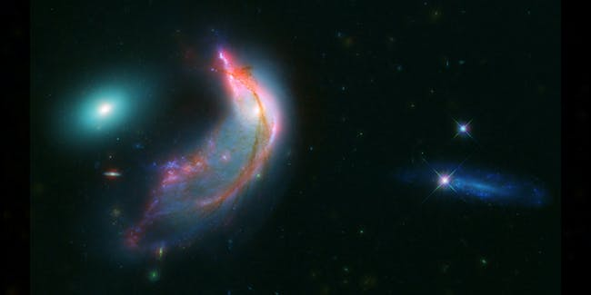 Interacting galaxies, known collectively as Arp 142, bears an uncanny resemblance to a penguin guarding an egg.