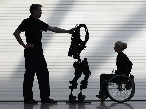LONDON, ENGLAND - OCTOBER 21:  Engineer Thomas Dwyer stands with the new Bionic Exoskeleton next to Amanda Boxtel during its launch at the Excel centre on October 21, 2011 in London, England. The bionic device developed by Ekso Bionics is a wearable, battery-powered, robotic exoskeleton, designed to aid wheelchair users and those who have suffered from spinal chord injuries to stand and walk.  (Photo by Dan Kitwood/Getty Images)