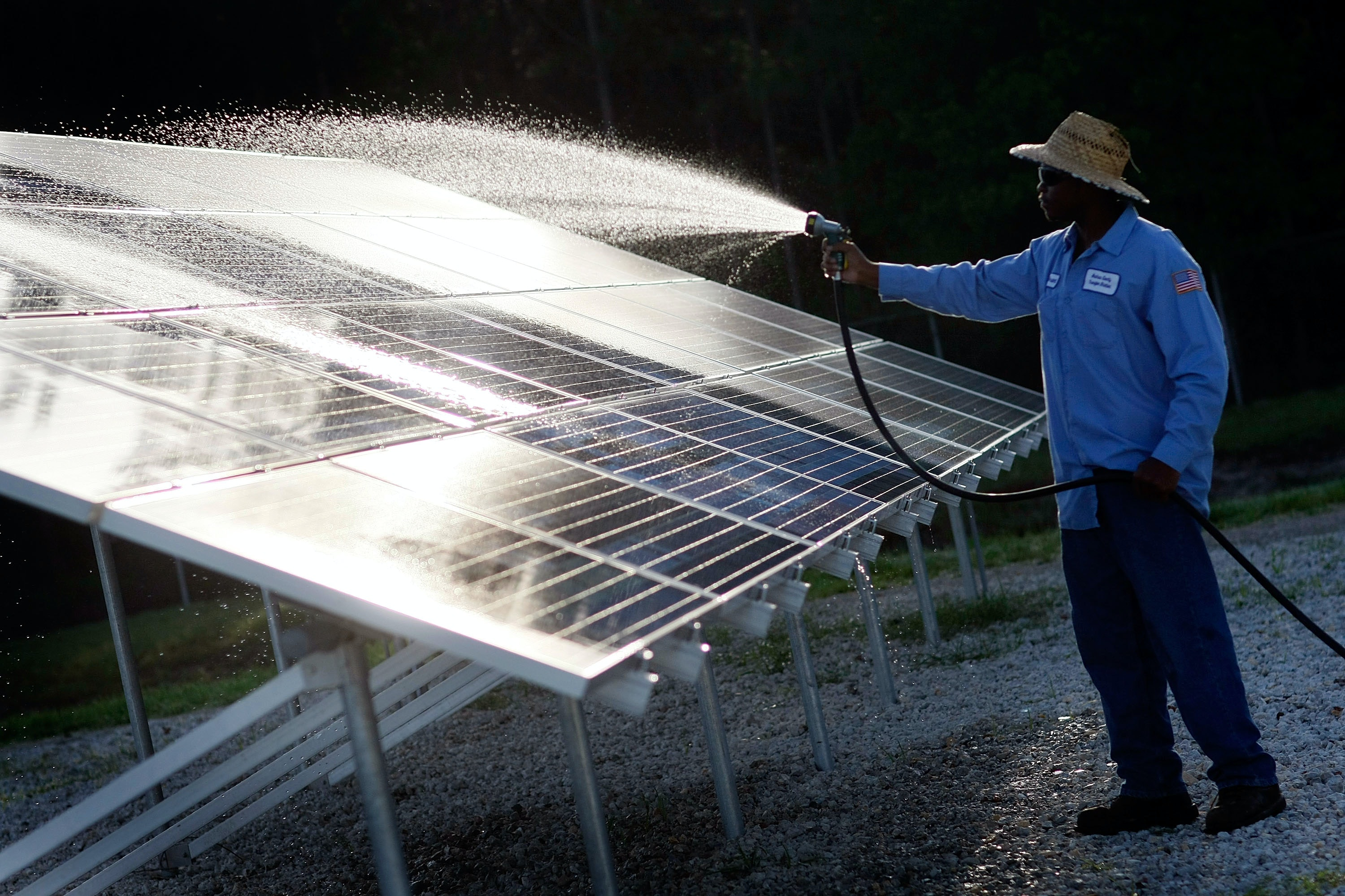 kindrell hutchinson washes off a solar panel system at the leveda brown park and transfer
