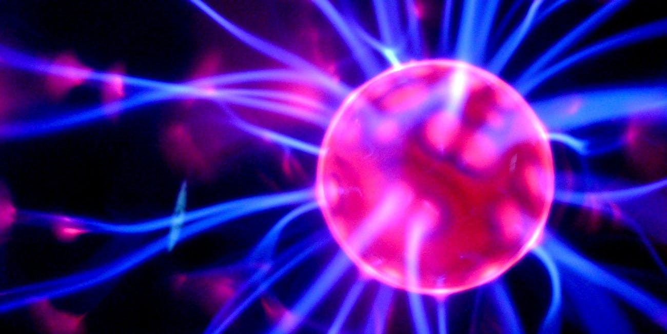 "Closeup of the interior of a ""plasma globe"" consisting of an electrode inside a partially evacuated glass globe, to which a high frequency AC voltage from a Tesla coil circuit is applied. The high frequency currents cause plasma streamers which extend to the glass surface. The name of this image is misleading, it is not an electrostatic generator."