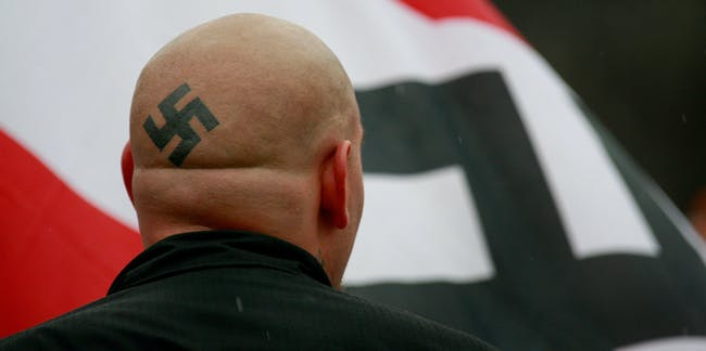 SKOKIE, IL - APRIL 19:  Neo-Nazi protestors organized by the National Socialist Movement demonstrate near where the grand opening ceremonies were held for the Illinois Holocaust Museum & Education Center April 19, 2009 in Skokie, Illinois. About 20 protestors greeted those who left the event with white power salutes and chants.  (Photo by Scott Olson/Getty Images)