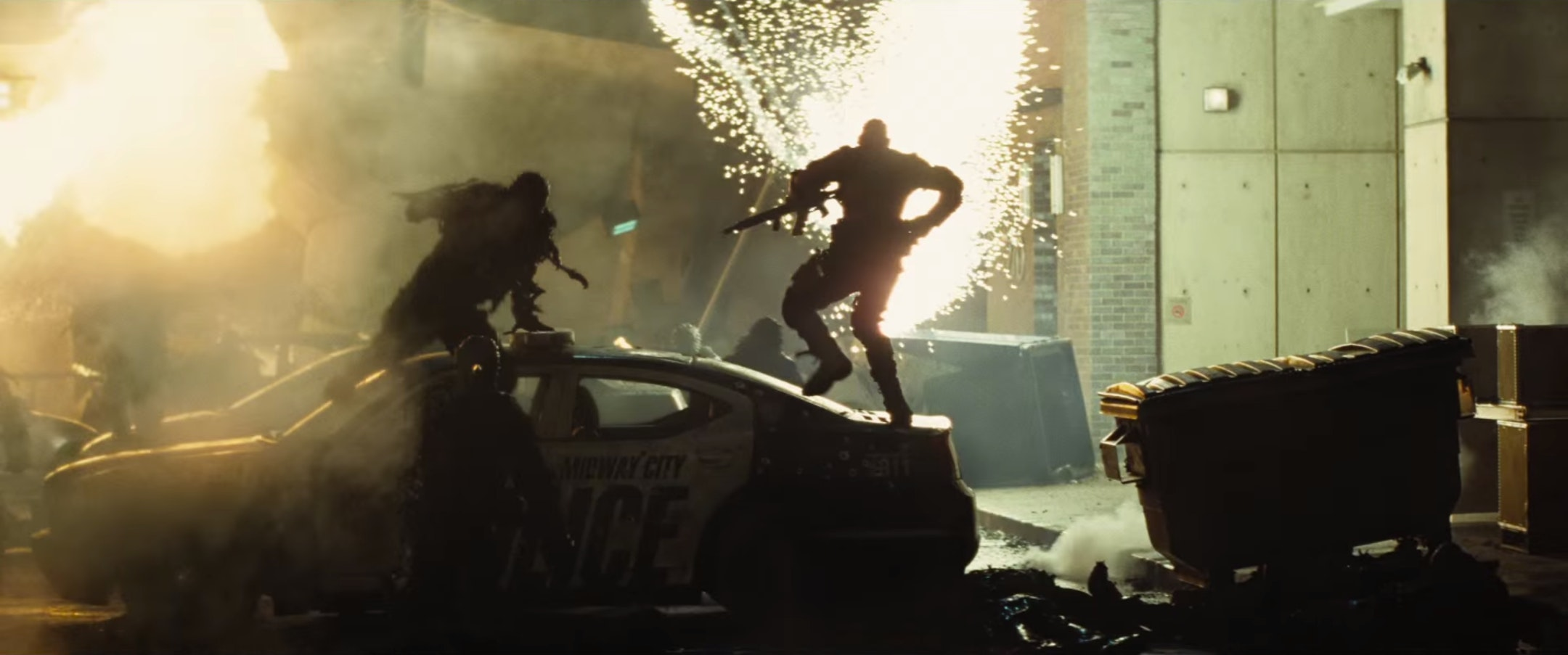Deadshot (Will Smith) climbs atop a Midway City police car in the 'Suicide Squad' trailer.