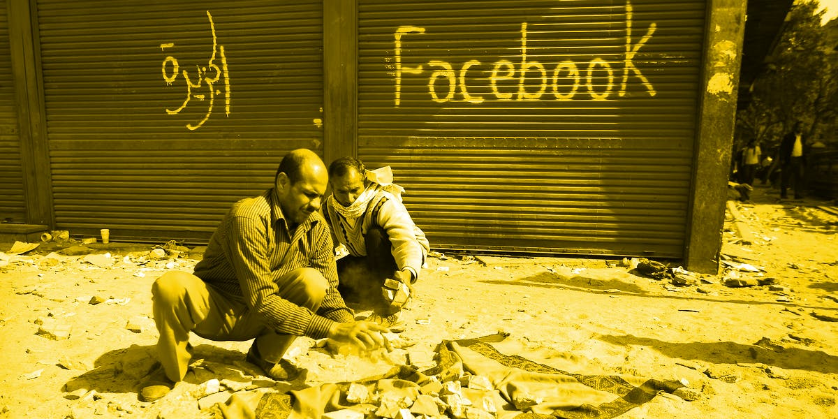 """Protestors during the Arab Spring movement break stones to defend Tahrir Square. The shop behind them has """"Facebook"""" spray-painted on it, symbolizing the social network's importance to the revolution that started in 2010."""