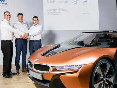 Brian Krzanich, CEO of Intel, Harald Krüger, Chairman of the Board of Management of BMW AG, and Amnon Shashua, Mobileye Co-Founder, Chairman and CTO Professor putting their hands together to make self-driving cars.