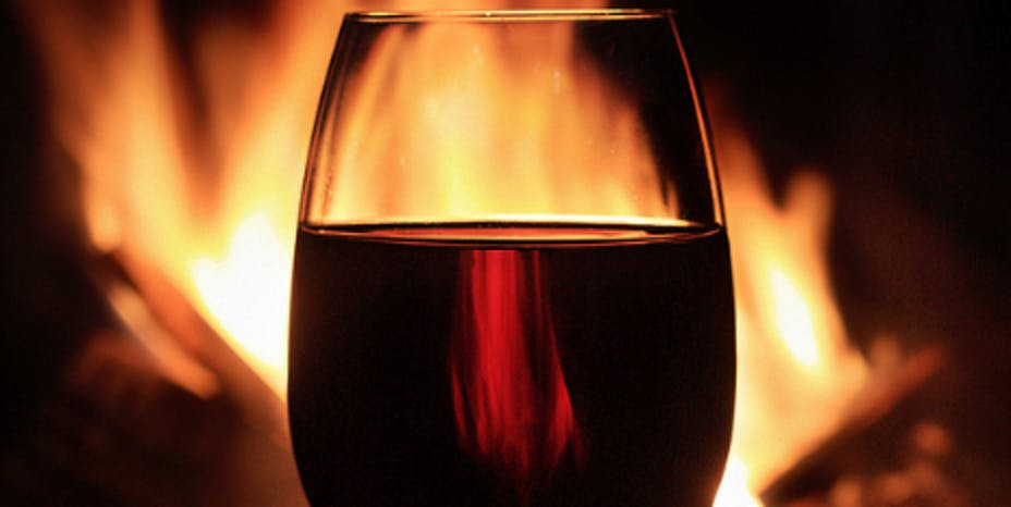 A glass of red wine in front of fire.
