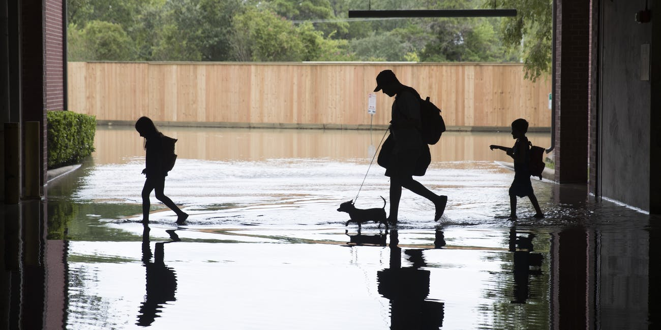 HOUSTON, TX - AUGUST 30: The Martinez family evacuates the apartment complex they live in near the Energy Corridor of west Houston, Texas where high water coming from the Addicks Reservoir is flooding the area after Hurricane Harvey on August 30, 2017 in Houston, Texas. Harvey, which made landfall north of Corpus Christi August 25, has dumped more than 50 inches of rain in some areas in and around Houston. (Photo by Erich Schlegel/Getty Images)