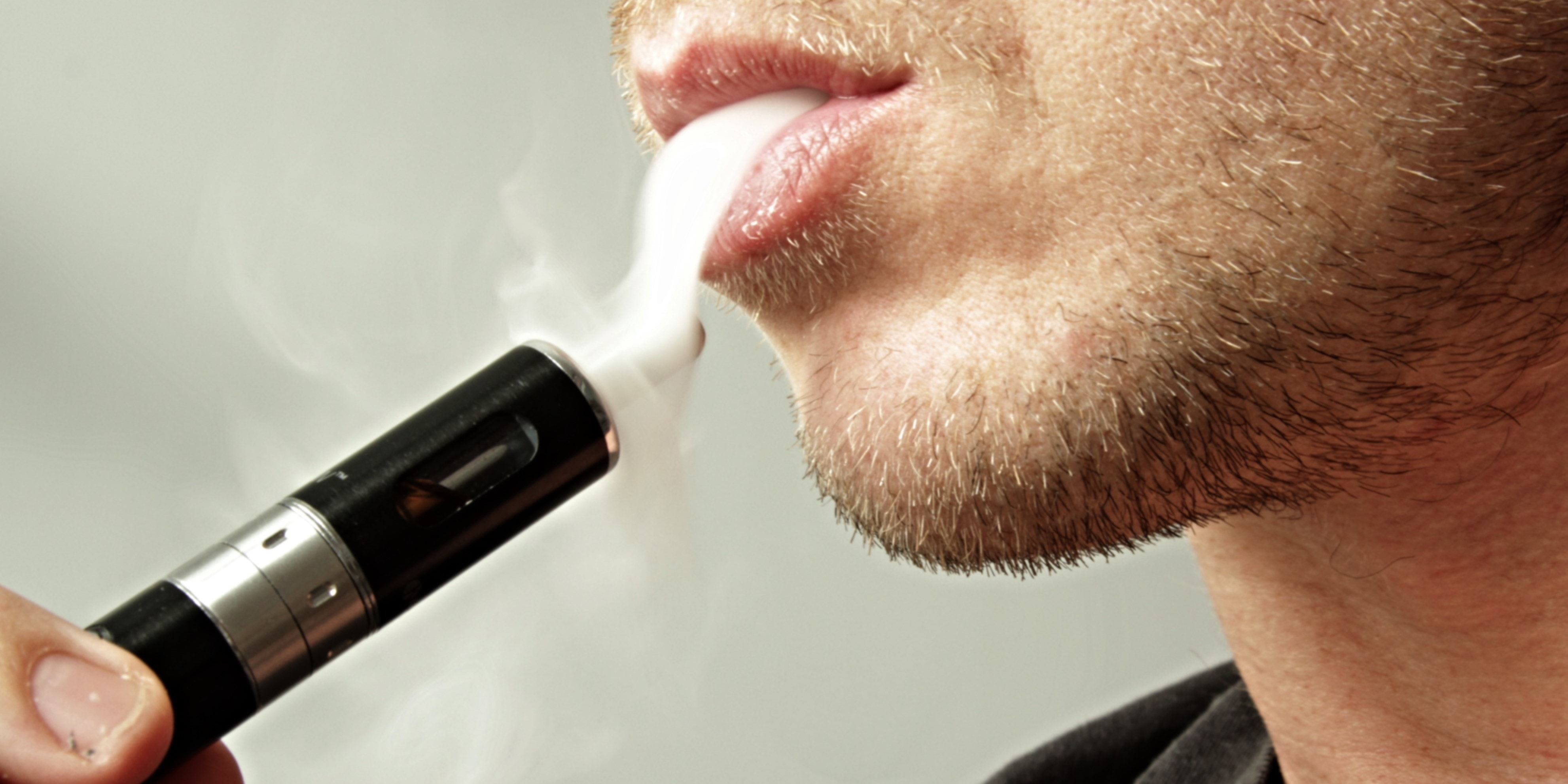 E Cigarette User Exhaling Vapor Smoke - Vape Pen e cig Device