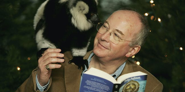 LONDON - DECEMBER 17: Author Philip Pullman unveils his 'Find Your Daemon' Christmas trail and exhibition at London Zoo on December 17, 2004 in London. Dana, the cheeky black and white lemur, is perched on Pullman's shoulder. The exhibition is based on 'His Dark Materials' trilogy of books, helps visitors to the zoo find their own daemon. (Photo by MJ Kim/Getty Images)