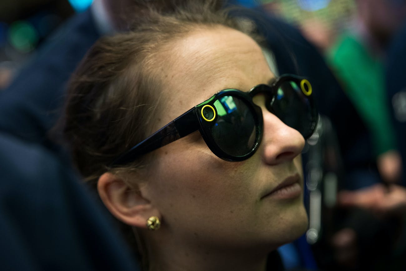 A woman wears 'Snapchat Spectacles' on the floor of the New York Stock Exchange (NYSE).
