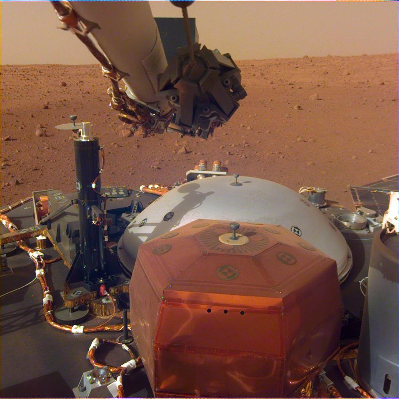 This image from InSight's robotic-arm mounted Instrument Deployment Camera shows the instruments on the spacecraft's deck, with the Martian surface of Elysium Planitia in the background.