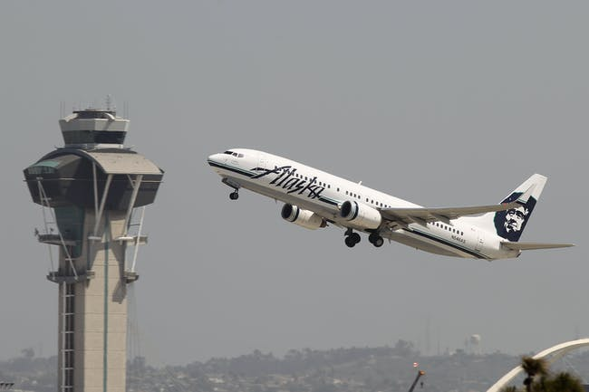An Alaska Airlines jet passes the air traffic control tower at Los Angles International Airport (LAX) during take-off on April 22, 2013 in Los Angeles, California. Delays have been reported throughout the nation because of the furloughing of air traffic controllers under sequestration. The average delay overnight in the Southern California Terminal Radius Approach Control (TRACON) was was three hours.