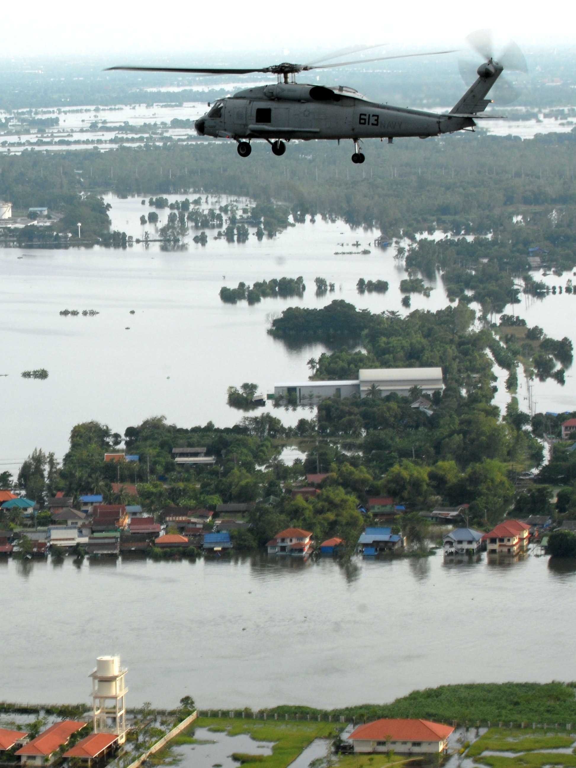 An SH-60F Sea Hawk helicopter assigned to Helicopter Anti-Submarine Squadron (HS) 14, flies around the Bangkok area with members of the humanitarian assessment survey team and the Royal Thai Armed Forces to assess the damage caused by flooding.