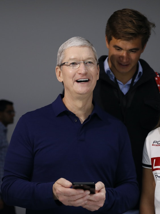 Apple CEO Tim Cook (2nd L) shows a iPhone 7 to members of the U.S. Olympic Team during a launch event on September 7, 2016 in San Francisco, California. Apple Inc. unveiled the latest iterations of its smart phone, the iPhone 7 and 7 Plus, the Apple Watch Series 2, as well as AirPods, the tech giant's first wireless headphones.