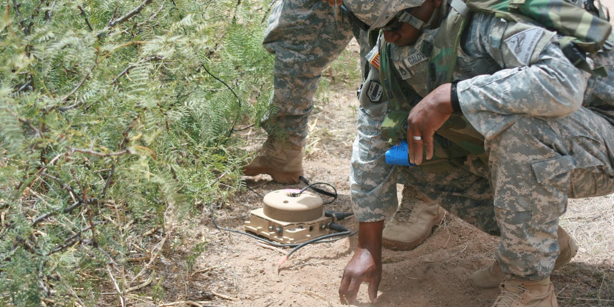 A soldier setting up a Tactical Unattended Ground Sensor (T-UGS) as part of a training exercise.