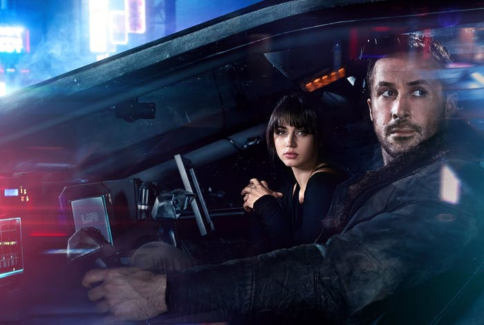 Ryan Gosling and Ana de Armas ride in a car that has a bunch of screens and, for some reason, a control lever.