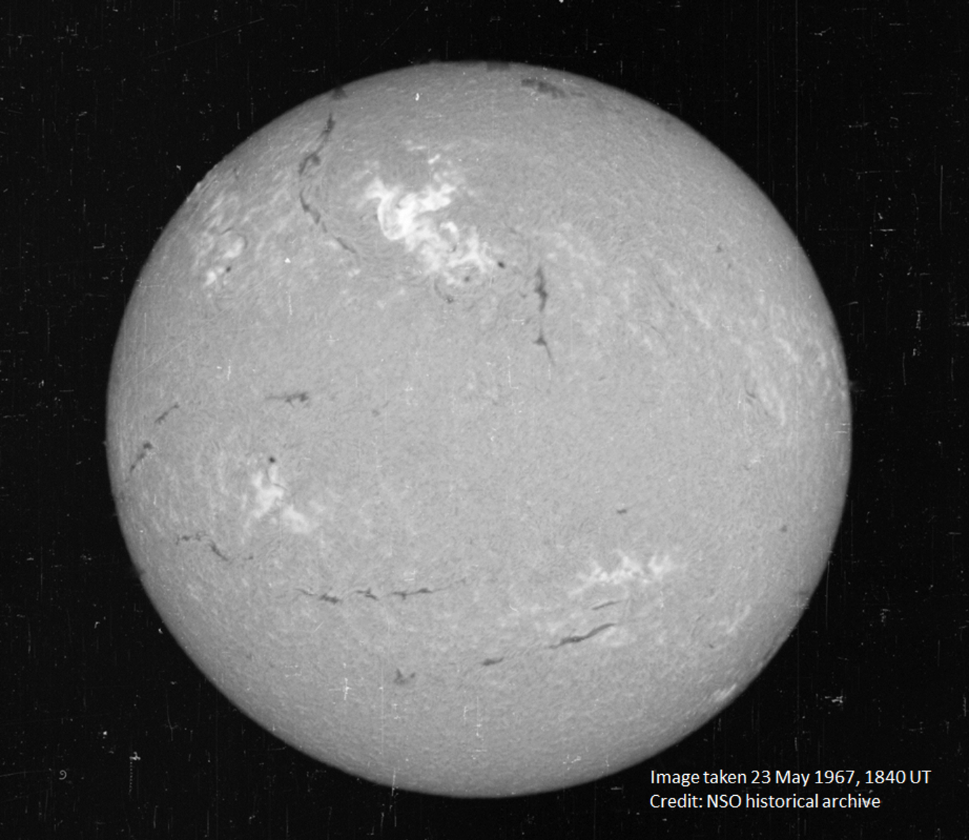 A view of the Sun on May 23, 1967, in a narrow visible wavelength of light called Hydrogen-alpha. The bright region in the top center region of brightness shows the area where the large flare occurred.