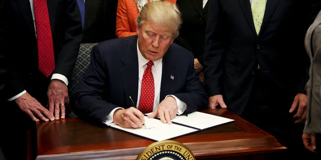 President Donald Trump signs an Executive Order to begin the roll-back of environmental regulations put in place by the Obama administration February 28, 2017 in the Roosevelt Room of the White House in Washington, D.C. The Clean Water Rule, also known as WOTUS, the Waters of the U.S. rule, has been unpopular with some farmers, housing developers and energy companies.