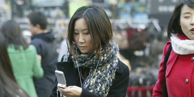 SEOUL, SOUTH KOREA - JANUARY 9: A South Korean sends a text massage on a mobile phone in the street on January 9, 2006 in Seoul, South Korea. Most S. Korean youths see mobile phones as an essential part of their social life, changing their conversation behaviour patterns. A survey conducted by the Korea Agency for Digital Opportunity and Promotion, an arm of the Ministry of Communication, reported of 1,100 students tested 4 in 10 send and receives text messages during class time and that the same amount send over 1,000 text messages a month.  (Photo by Chung Sung-Jun/Getty Images)