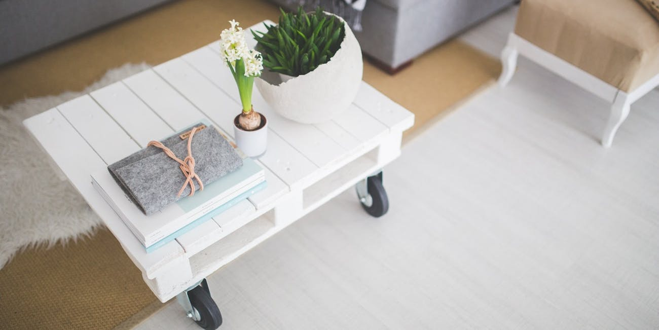 A small white table on wheels with a book and two plants on it.