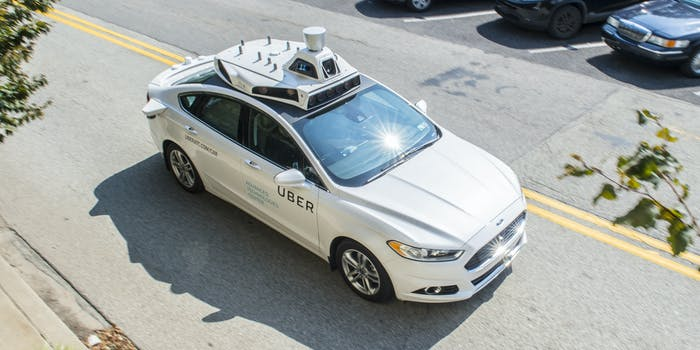 Photo shows an Uber self-driving car in motion and at rest in Pittsburgh.