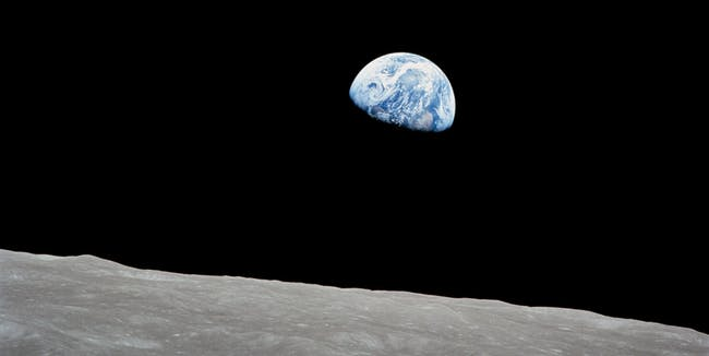 The rising Earth is about five degrees above the lunar horizon in this telephoto view taken from the Apollo 8 spacecraft near 110 degrees east longitude.