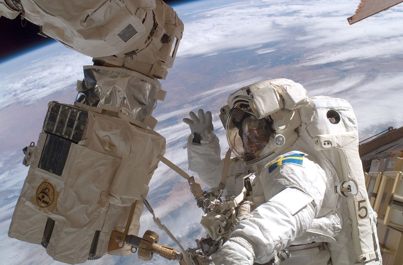 IN SPACE - DECEMBER 14: Mission specialist Christer Fuglesang waves to the camera as he participates in the second of three planned space walks during construction on the International Space Station on Day 6 December 14, 2006 in orbit around the Earth. Mission specialist Robert L. Curbeam, Jr. also participated. (Photo by NASA via Getty Images)
