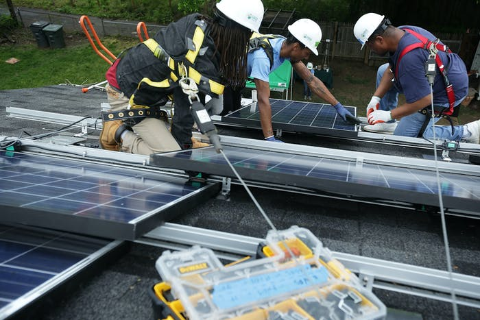 WASHINGTON, DC - MAY 03:  Workers put solar panels down during an installation May 3, 2106 in Washington, DC. The installation marked the one millionth in the U.S. in the past 40 years. It has been predicted that the U.S. will reach 2 million installations in two years.  (Photo by Alex Wong/Getty Images)