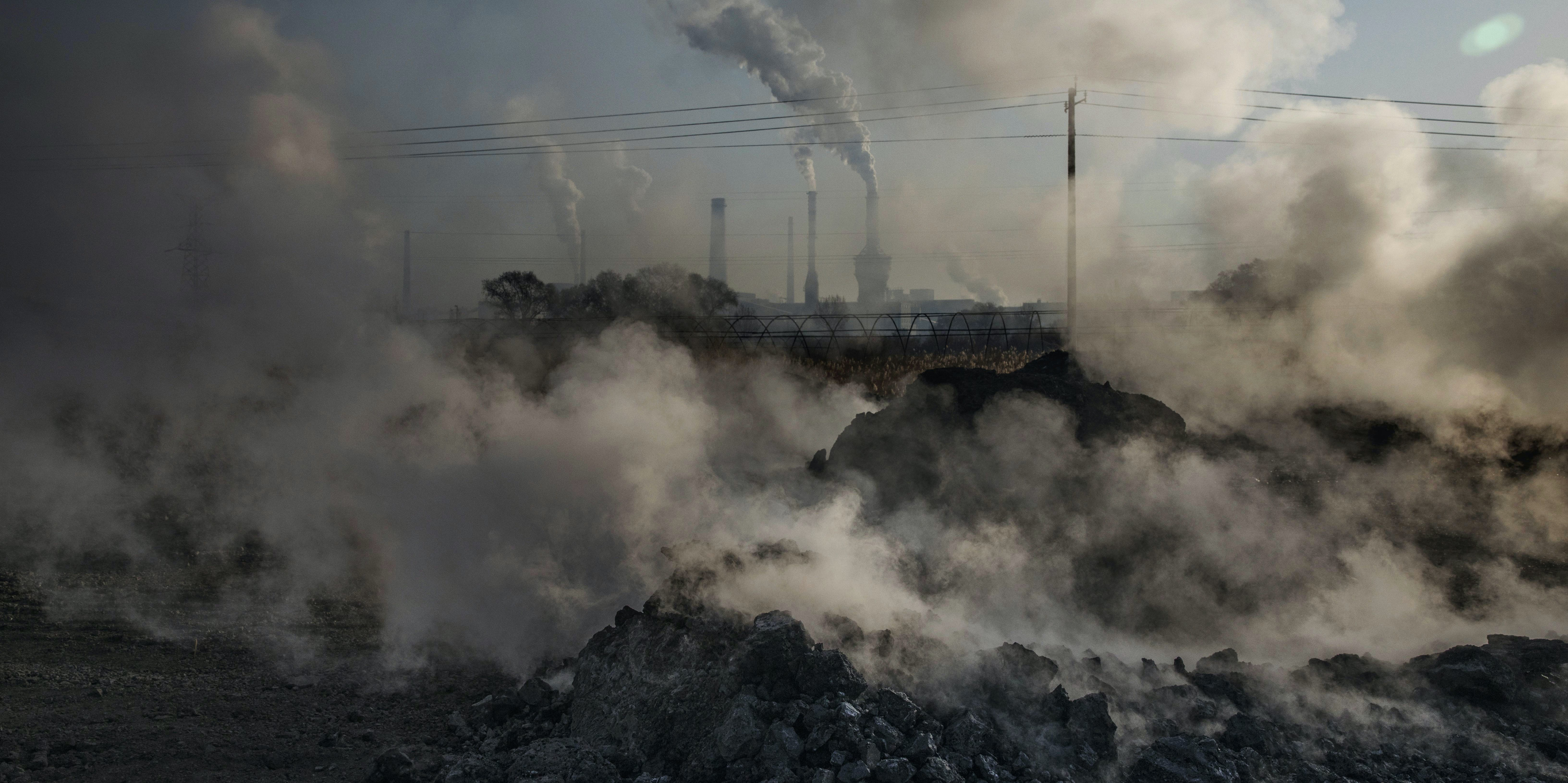 Steam and smoke from waste coal and stone rises after being dumped next to an unauthorized steel factory on November 3, 2016 in Inner Mongolia, China. To meet China's targets to slash emissions of carbon dioxide, authorities are pushing to shut down privately owned steel, coal, and other high-polluting factories scattered across rural areas. In many cases, factory owners say they pay informal 'fines' to local inspectors and then re-open. The enforcement comes as the future of U.S. support for the 2015 Paris Agreement is in question, leaving China poised as an unlikely leader in the international effort against climate change. U.S. president-elect Donald Trump has sent mixed signals about whether he will withdraw the U.S. from commitments to curb greenhouse gases that, according to scientists, are causing the earth's temperature to rise. Trump once declared that the concept of global warming was 'created' by China in order to hurt U.S. manufacturing. China's leadership has stated that any change in U.S. climate policy will not affect its commitment to implement the climate action plan. While the world's biggest polluter, China is also a global leader in establishing renewable energy sources such as wind and solar power.