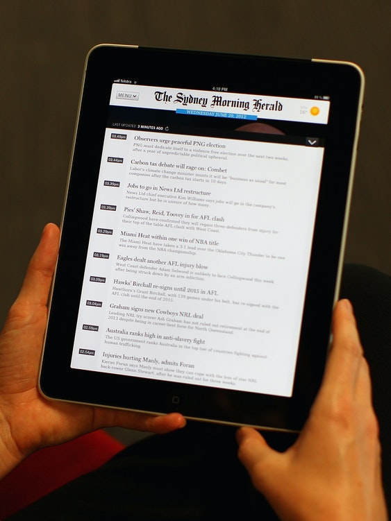 In this photo illustration a woman uses the Sydney Morning Herald app on an iPad on June 20, 2012 in Sydney, Australia.