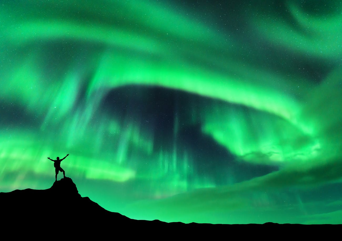 Aurora borealis and silhouette of a man with raised up arms on the mountain peak. Lofoten islands, Norway.