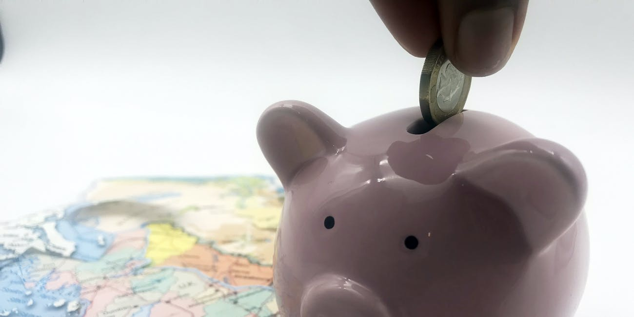 A pink piggy bank sits next to a map of a country to represent Offshore Tax Havens
