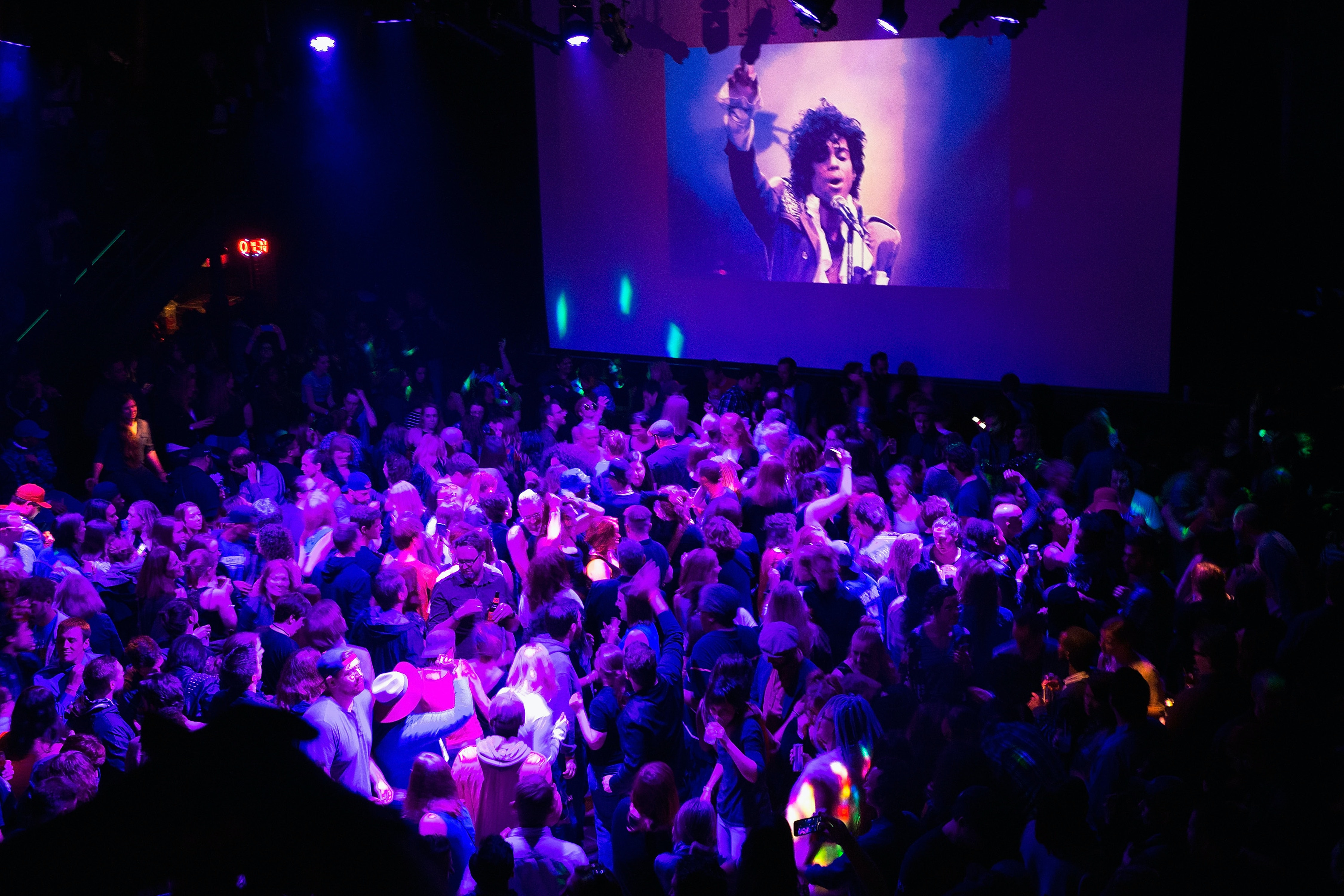 MINNEAPOLIS, MN - APRIL 21: Guests dance to Prince music as a slide show flashes images of the artist above the stage during a memorial dance party at the First Avenue nightclub on April 21, 2016 in Minneapolis, Minnesota. Prince, 57, was pronounced dead shortly after being found unresponsive at Paisley Park Studios in Chanhassen, Minnesota near Minneapolis. (Photo by Scott Olson/Getty Images)